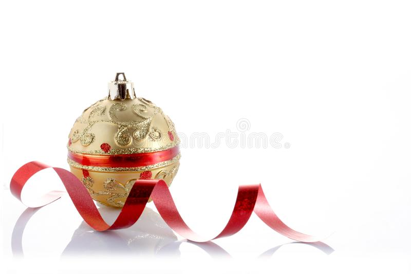 Golden Christmas ball and a golden ribbon isolated on white background with copy space royalty free stock photos