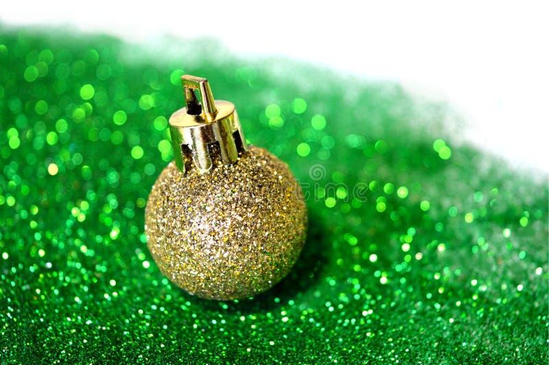 Golden Christmas ball on green glitter on white background. Golden Christmas ball on green glitter on the white background royalty free stock images