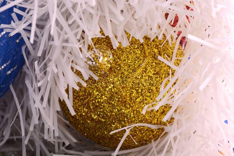 Golden christmas ball on shining glitter background close-up. Golden christmas ball on shining glitter background close up stock photo