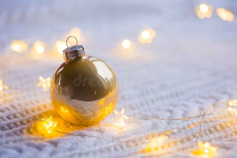 Golden Christmas ball with warm garland lights on white knitted stock photography