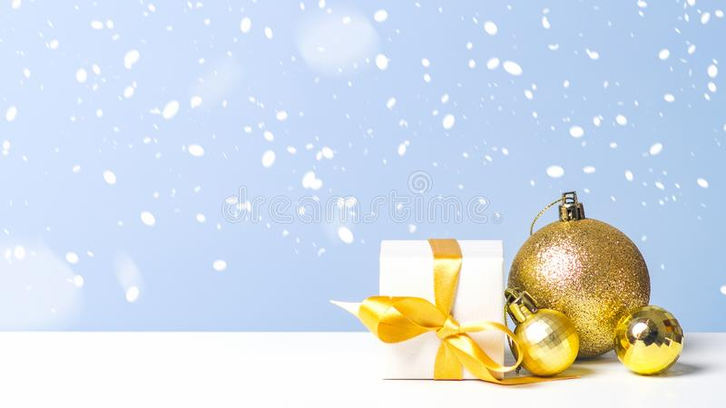Golden Christmas balls and gift box with gold ribbon bow in snow on blue background. Christmas, New Year, winter holidays concept stock image