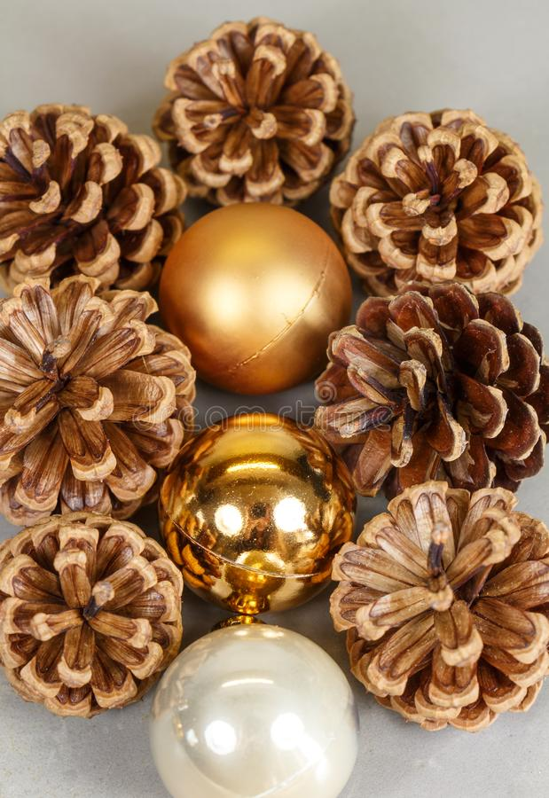 Golden Christmas balls and pine cones. Golden and pearly baubles and pine cones as decoration for Christmas royalty free stock image