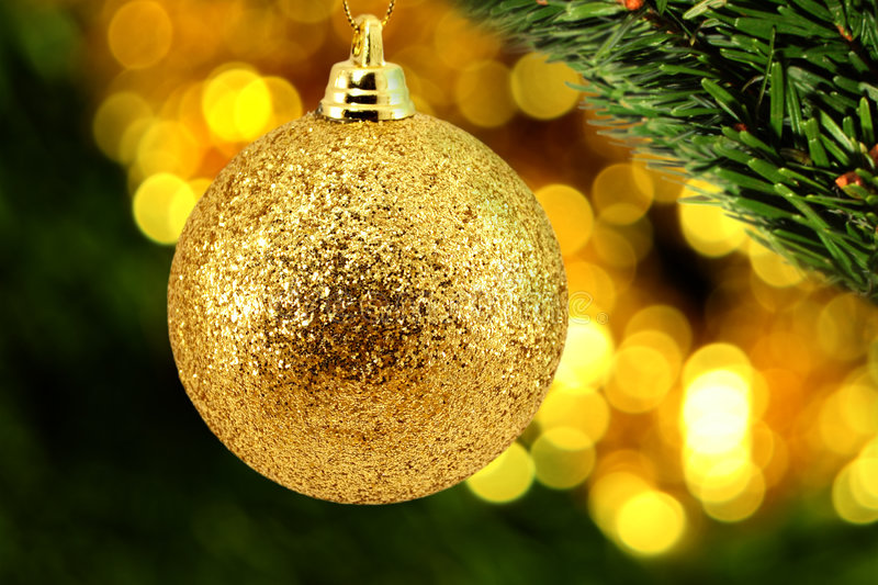 Golden Christmas Bauble With A Leaf Of Evergreen Stock Photo