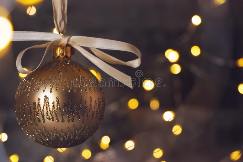 Golden christmas bauble on shiny blackground royalty free stock images