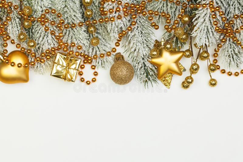 Golden Christmas composition border with green Xmas tree twig and New Year decoration isolated on white background.  stock photos