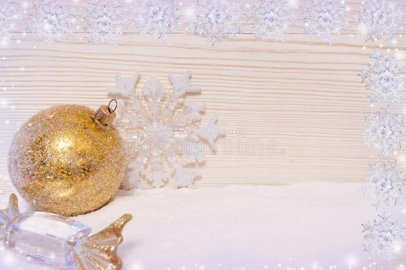Golden Christmas decorations ball, candy and snowflake are lying on snow on wooden background with snowflakes. Christmas card. Two rows of snowflakes, golden stock image