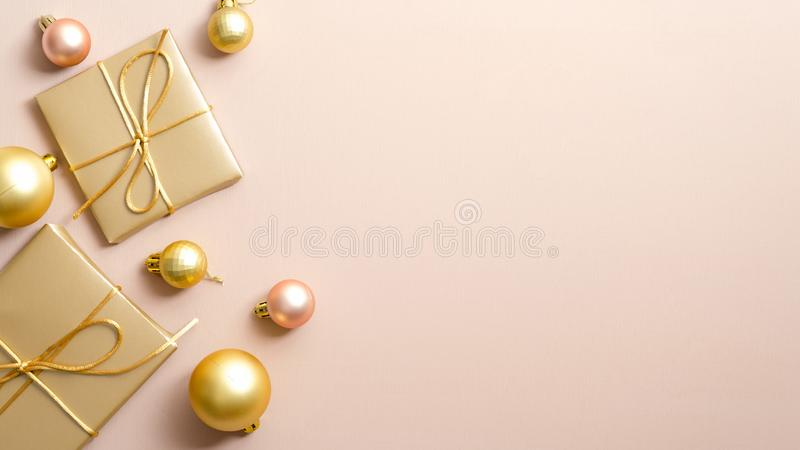 Golden Christmas gifts and balls on pastel beige background with copy space. Glamour Xmas banner design with elegant stylish. Decorations. New Year greeting royalty free stock photos