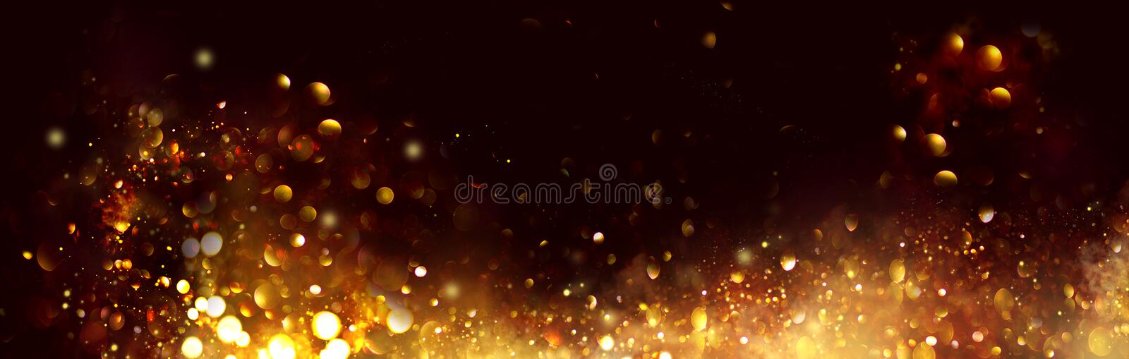 Golden Christmas and New Year glittering stars swirl on black bokeh background, backdrop with sparkling golden stars royalty free stock photos