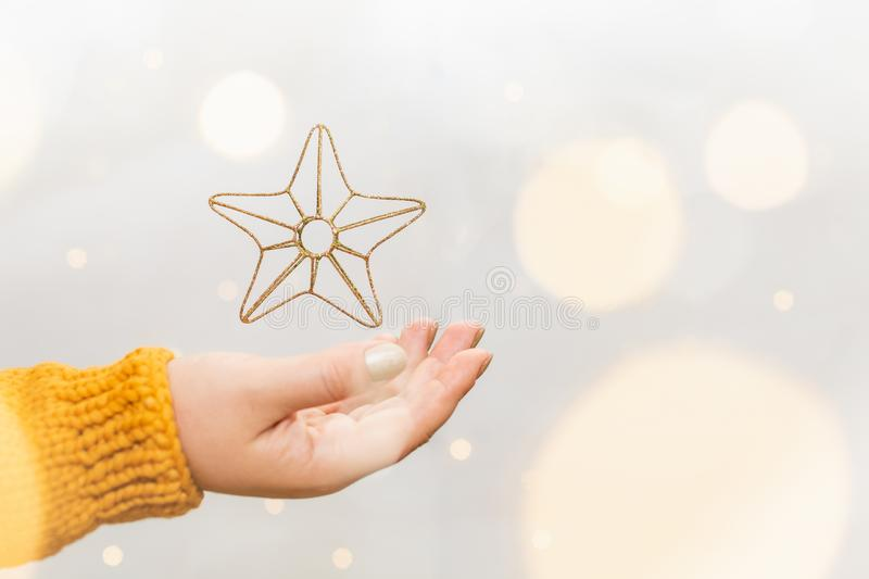 Golden Christmas star levitating above female hand in orange sweater, garland bokeh on background. Levitation, lights, woman, happy, new, year, celebration royalty free stock photo