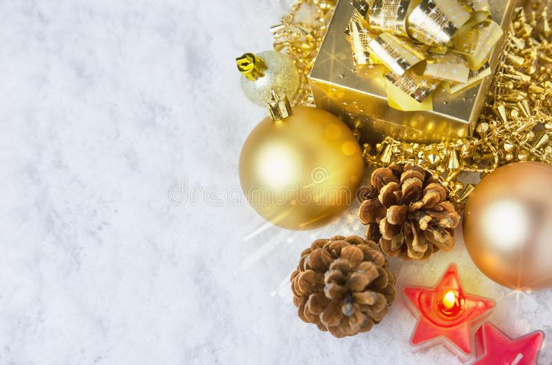 Golden Christmas toys on snow with bright light and bokeh royalty free stock photo
