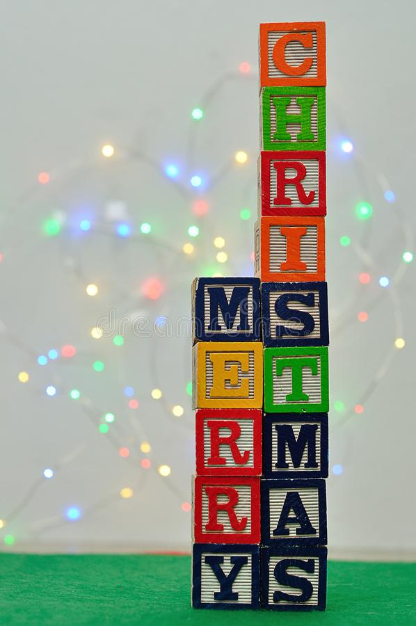 A golden christmas tree and the words Merry Christmas against an out of focus light background. And a green background royalty free stock image
