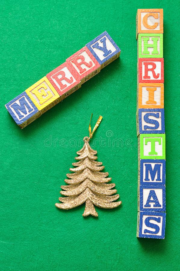 A golden christmas tree and the words Merry Christmas. On a green background royalty free stock images