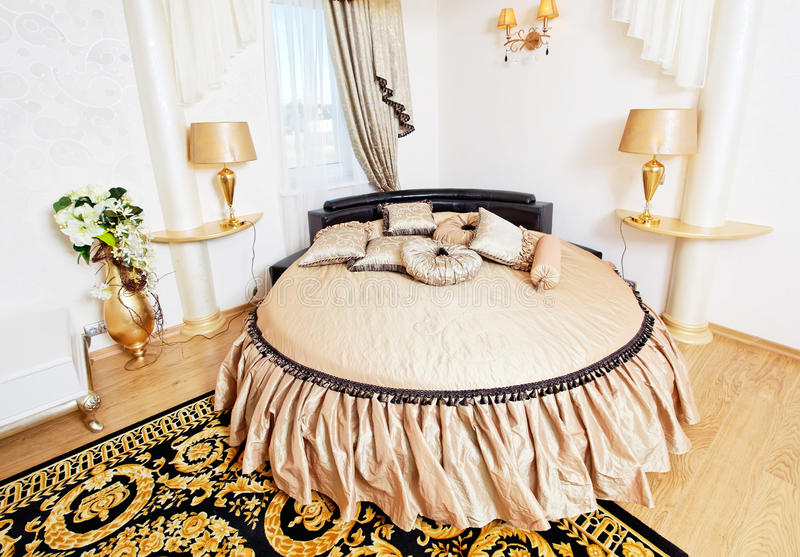 Golden classical bedroom interior with round bed, carpet and small table. Golden classical bedroom interior with round bed and carpet royalty free stock photo