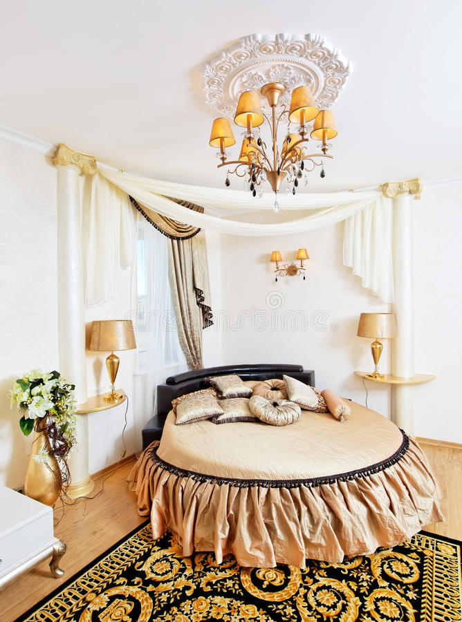 Golden classical bedroom interior with round bed. And ornate ceiling royalty free stock photo