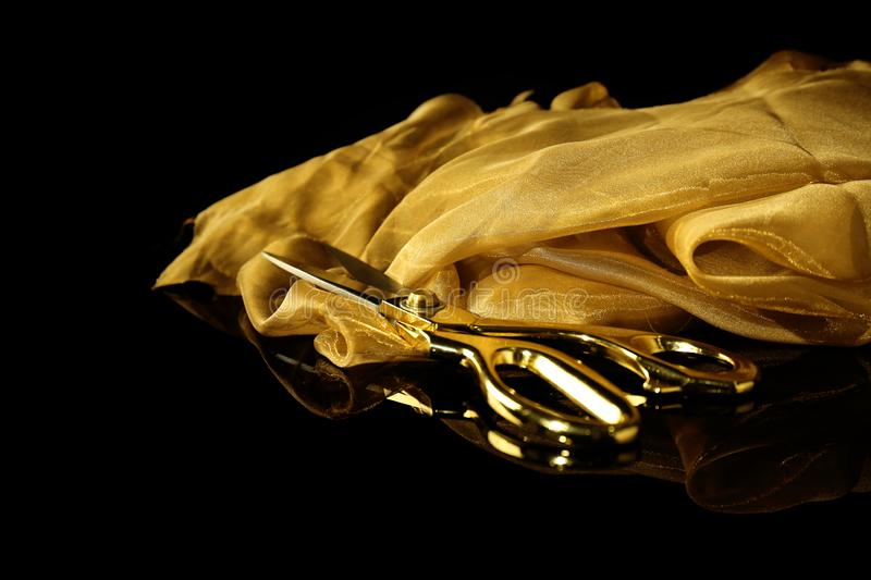 Golden cloth with scissors on black background stock photography