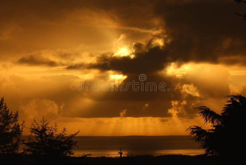 Golden Cloudburst. Over the harbor at sunset showing spectacular crepuscular rays and dramatic storm clouds royalty free stock photo