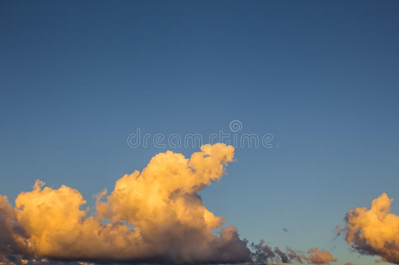 Golden clouds bathed by the sunset, in a beautiful blue sky royalty free stock images