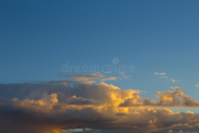 Golden clouds bathed by the sunset, in a beautiful blue sky.  stock image