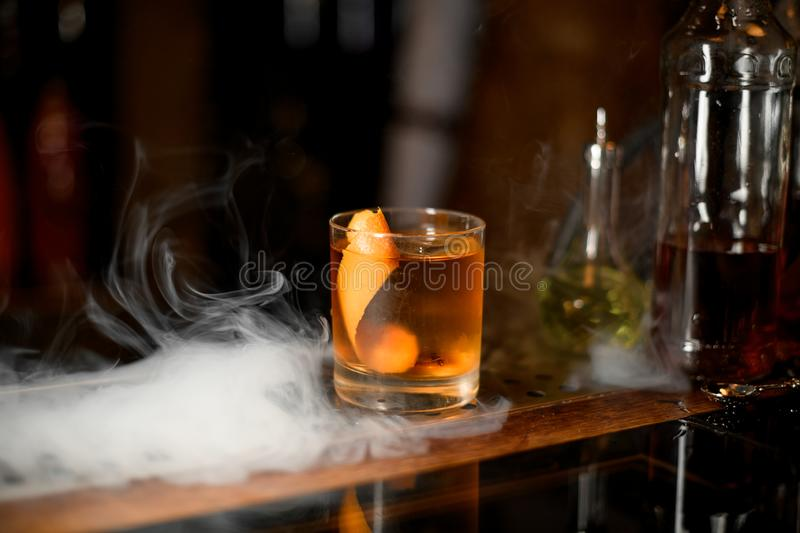 Golden cocktail in the glass with one ice cube and orange zest in the smoke stock photos