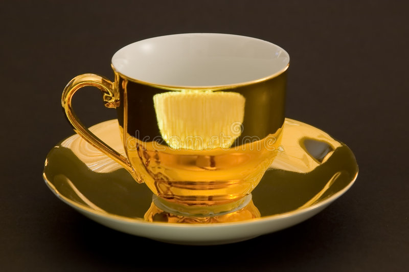 Golden coffee cup. On a black background stock image