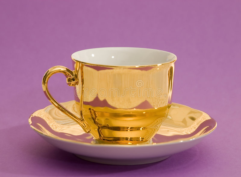 Golden coffee cup. On a violet background royalty free stock photos