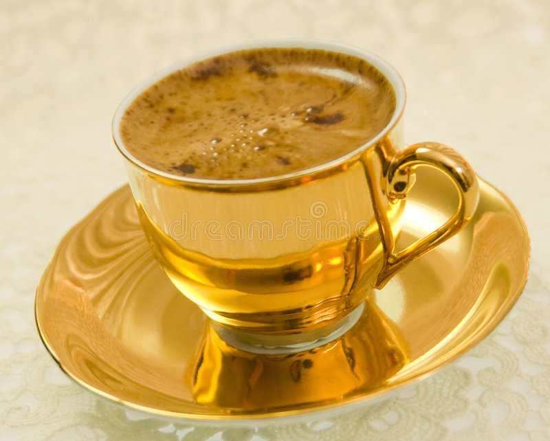 Golden coffee cup. On a tablecloth royalty free stock photos