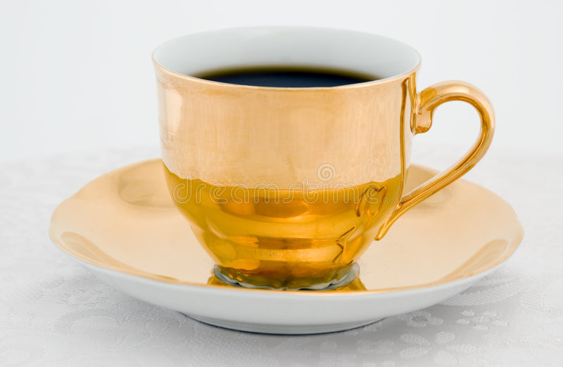 Golden coffee cup. On a white background stock images