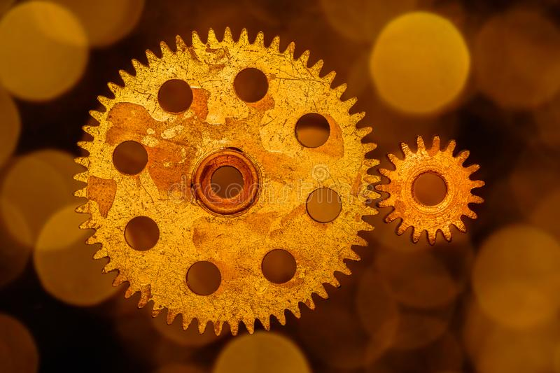 Golden cogwheels on a background of gold circled bokeh. Two golden cogwheels on a background of gold circled bokeh. 50 yrs old cogwheels stock photo