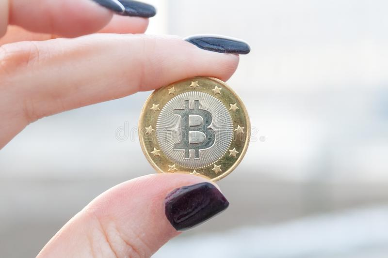 Golden coin bitcoin between the thumb and index fingers of a female hand with dark nails. Blurred background. Closeup view stock photography