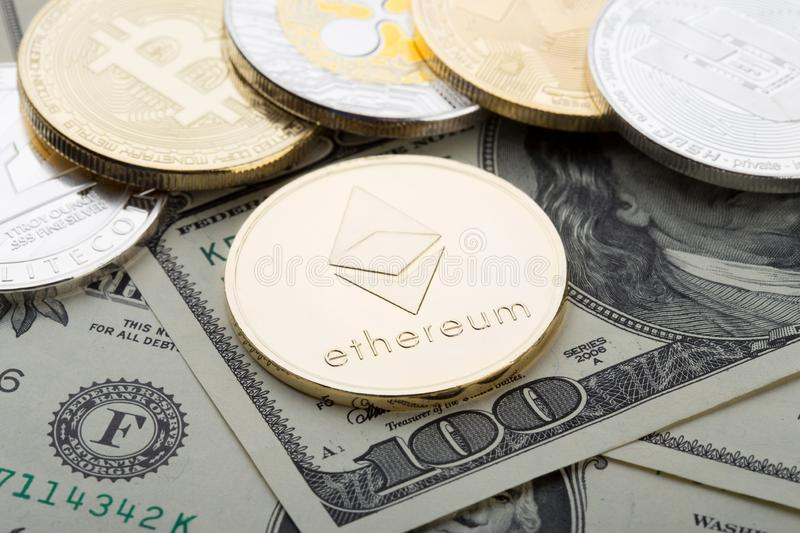 Golden coin - ethereum crypto currency. Virtual currency on the hundred dollar bill. Gold coin - ethereum crypto currency. Virtual currency on the hundred dollar stock photo