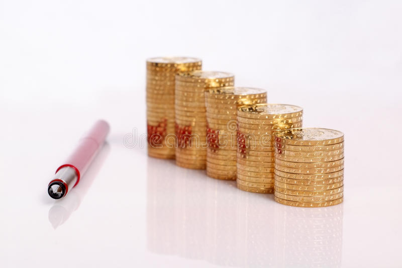 Golden coins and red pen. Stacks of golden coin and red pen an white background royalty free stock images