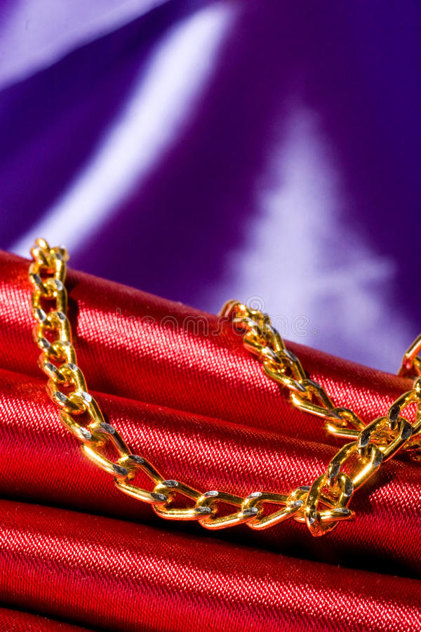 Golden color chain over red silk. Yellow metal, golden color chain over red silk stock images