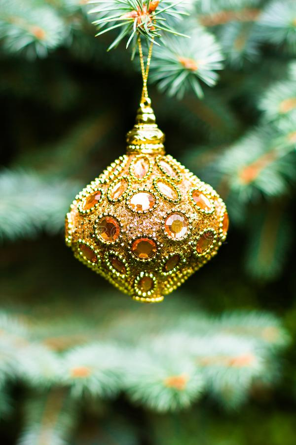 Golden colored christmas or new year toy decoration hanging on a christmas tree, selective focus. Christmas postcard. Holiday conc stock photo