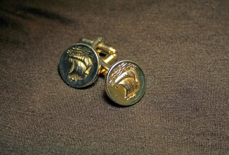 GOLDEN COLOURED CUFF LINKS ON A BROWN BACKGROUND stock photo