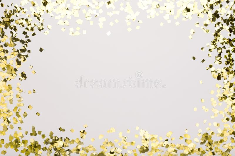 Golden confetti sparkling on white background with copy space. Frame border for text stock photos