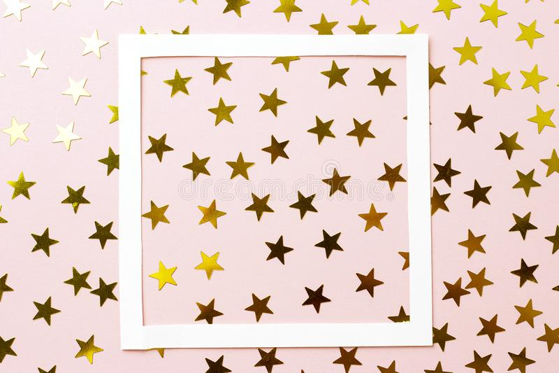 Golden confetti and white frame on a pink background, top view royalty free stock photo