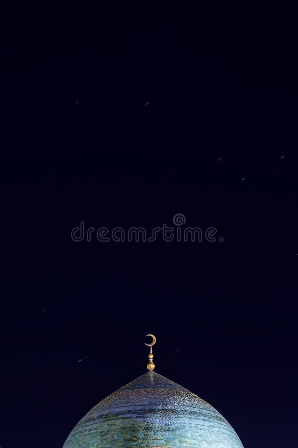 The golden crescent on the dome of the Mosque. Waxing moon - a symbol of Islam at the top of the temple at night sky with stars. royalty free stock photography