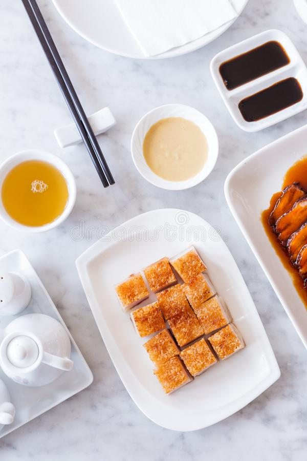 Golden Crispy Pork Belly cut in cube served with mustard sauce and hot tea with chopsticks royalty free stock photo