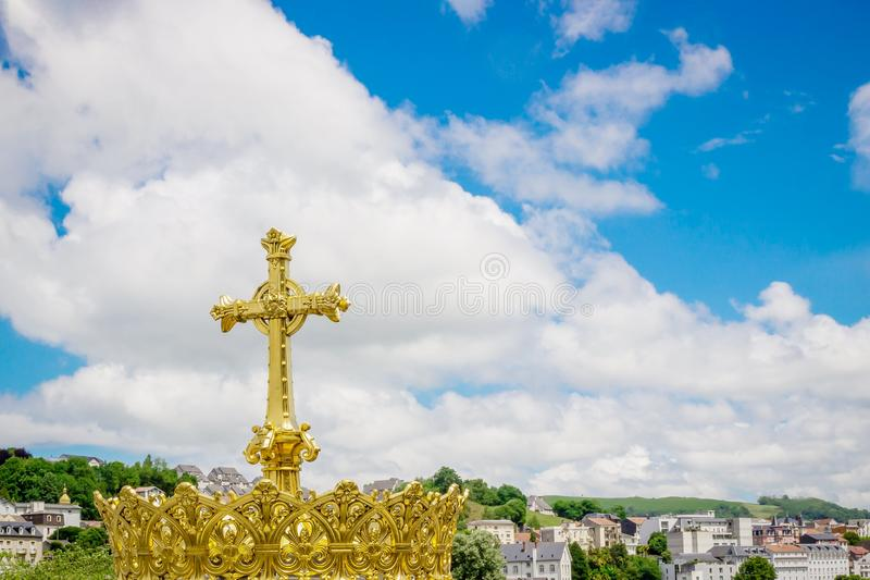 Golden cross and crown on the beautiful blue sky background. Lourdes France. Golden cross and crown on the beautiful blue sky background. Lourdes, France royalty free stock images