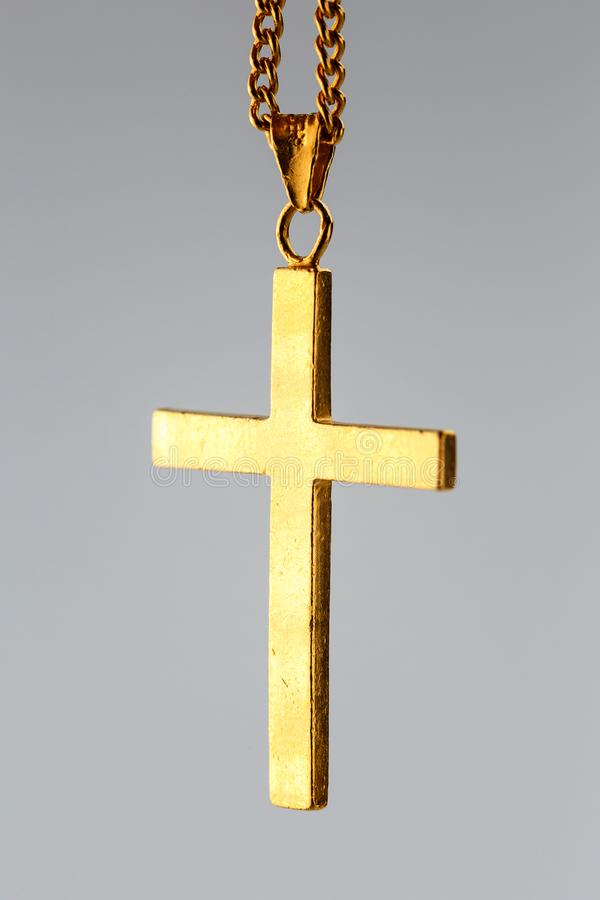 Golden cross pendant on the gold chain stock image