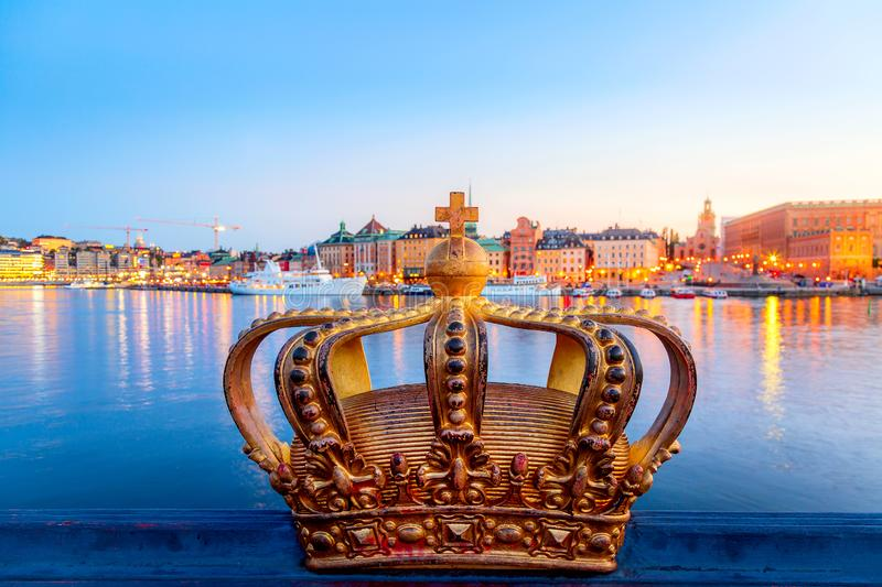 Golden crown on Skeppsholm bridge with illuminated Stockholm old city center Gamla Stan in the background during twilight sunset royalty free stock photo