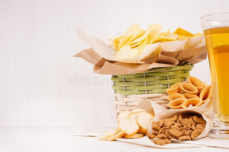 Golden crunchy snacks collection and lager beer in glass on soft white wood board. royalty free stock photo