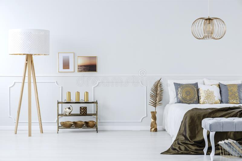Golden decorations in luxurious bedroom. Elegant, golden decorations in a luxurious, light gray bedroom interior with furniture and wall molding stock image