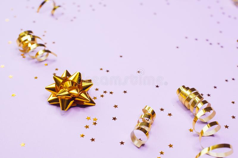 Golden decorations and sparkles on pale purple background. Golden decorations and sparkles on bright pale purple background royalty free stock photos