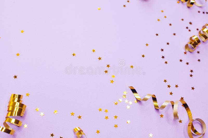 Golden decorations and sparkles on pale purple background. Golden decorations and sparkles on bright  pale purple background stock photo