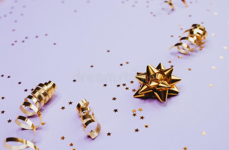 Golden decorations and sparkles on pale purple background. Golden decorations and sparkles on bright  pale purple background royalty free stock photo