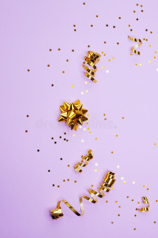 Golden decorations and sparkles on pale purple background. Golden decorations and sparkles on bright  pale purple background royalty free stock image