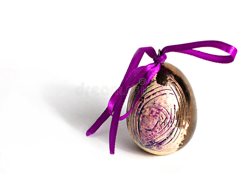 Golden decorative easter egg with purple ribbon royalty free stock photography