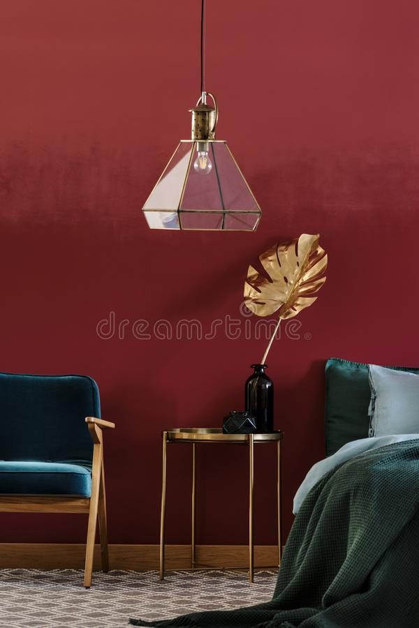 Golden decorative leaf. Golden, decorative leaf in glass vase standing on a metal bedside table between blue armchair and bed in bedroom interior stock photos