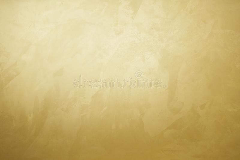 Golden decorative plaster texture with glow, photo. Golden decorative plaster texture with pearl glow stock photography
